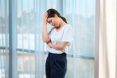 Young sad woman holds her head with her hand and cries. In the background of the window. The concept of domestic violence.
