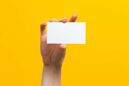Raised female hand holding a white card. Mock up. Yellow background. Copy space. Archivio Fotografico