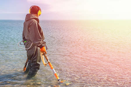 A man standing knee-deep in the water looking for precious metals with a metal detector. Sea and sky on the background. Light from the right side. History and archeology concept.