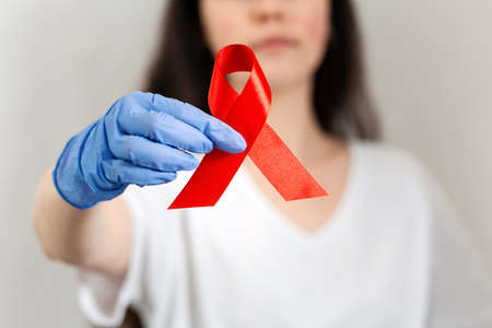 A woman in medical rubber gloves, holding a red ribbon with her fingers. Hands close-up. The background is blurred. The concept of world AIDS day.