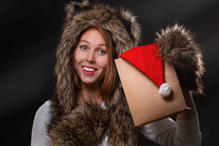 New Year. A beautiful young woman, in a fur hat with ears, and woolly mittens, smiling and holding a package with a Christmas hat. Black background. Horizontal. Stock fotó