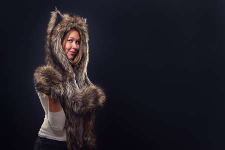 A young beautiful woman in a fur hat with ears, and woolly mittens, smiling provocatively. Black background and copy space.