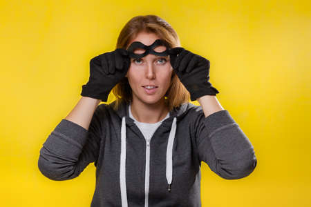 The concept of cybercrime and hacking. Portrait of a woman in black gloves, which removes the mask from her face. Yellow background. Stockfoto
