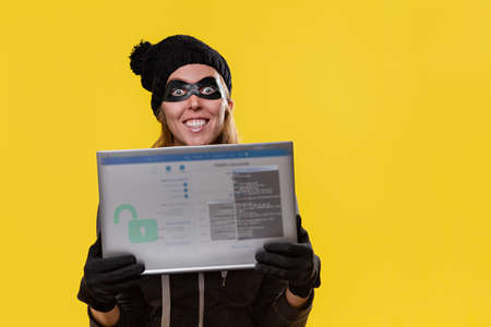 The concept of cybercrime and hacking. Portrait of a woman in a black hat, gloves and mask holding a transparent tablet with a password window and smiling ominously. Yellow background and copy.
