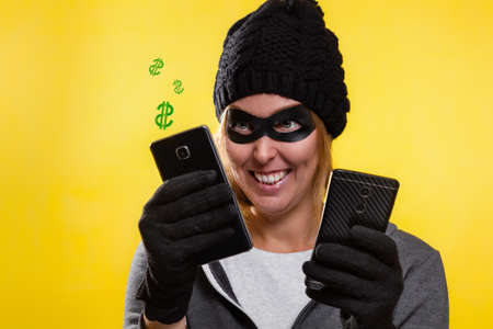 Cybercrime and money theft. A woman in a hat and mask with a malicious smile, holding phones from which fly signs of dollars. Yellow background and copy space.