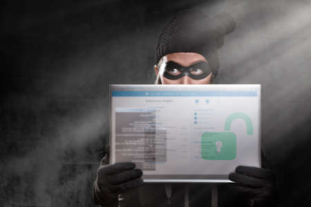 The concept of cybercrime and hacking. Portrait of a woman in a black hat, gloves and mask, who is holding a transparent tablet with a password window. Dark background. Copy space. Stock fotó - 159567683
