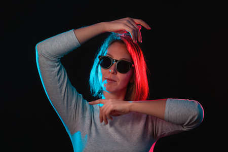 The neon lights of the club. Portrait of a young woman in glasses, posing with her hands. Side blue and red light. Black background. Stock fotó - 159567684