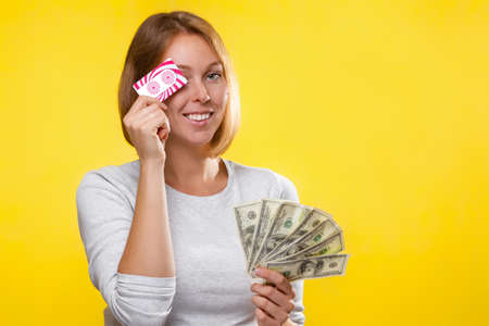 Finance and Bank cards. A young blonde holds a wad of dollars in her hands and, smiling, covers her eyes with a Bank card. Yellow background and copy space.