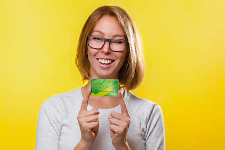 Bank cards and Finance. A young blonde woman with glasses, holding a Bank card with the index fingers of both hands. Yellow background. Copy space.