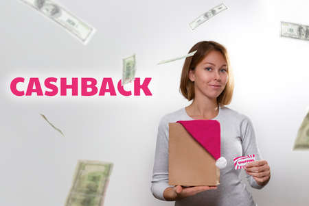 Shopping and Finance. A beautiful young woman with a smile holds a paper bag with a Christmas hat and a Bank card. Banknotes swirl in the air. Text CASHBACK.