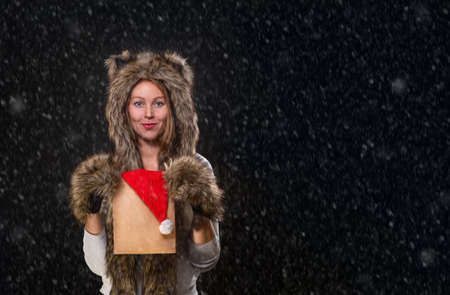 New Year. A beautiful young woman, in a fur hat with ears, and woolly mittens, smiling and holding a package with a Christmas hat. Black background, simulated snow. Copy space. Stock fotó