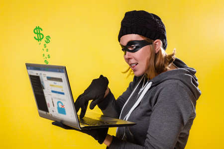 The concept of cybercrime and hacking. Portrait of a woman in a black hat, gloves and mask holding a laptop and engaged in hacking. Yellow background and dollar icons. Stock fotó