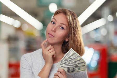 Finance and banking. A young blonde holds a wad of dollars in her hands and smiles sweetly. In the background is a blurred shop floor.