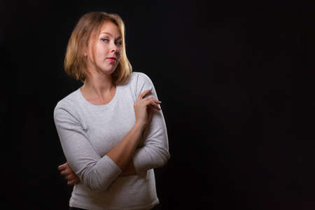 Portrait of a beautiful blonde young woman with her arms crossed over her chest. Black background. Copy space. Stock fotó