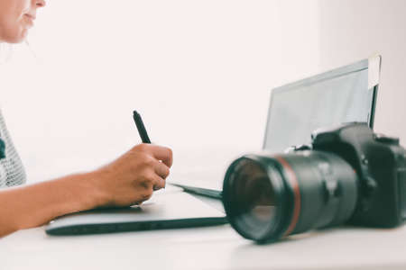Young woman using digital graphic tablet and drawing pen to retouch the images. Camera at the first plan. Close up. Stock fotó
