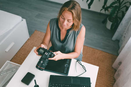 A young woman photographer sitting at his Desk and working with a camera. View from the top. Stock fotó
