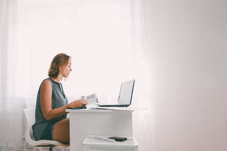 A young woman sitting at a table and leafing through a book. Nearby are a laptop and office supplies. Interior is white color. Copy space.