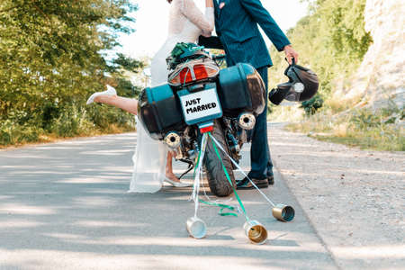 Wedding, newlyweds. Hugs and kisses of a man and a woman in wedding dresses, near a motorcycle. Road on the background. Stock fotó - 159617887