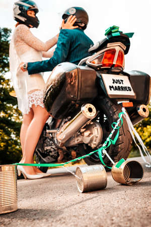 Wedding, newlyweds. A man and a woman in wedding and motorcycle helmets, hugging near a motorcycle, in a blur. The back of the bike close up. Bottom view.