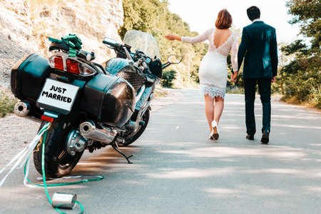 Wedding, newlyweds. A man and a woman in wedding dresses hold each other's hands and walk along the road. Their motorcycle is parked on the side of the road. Rear view. Summer. Close up. Stock fotó