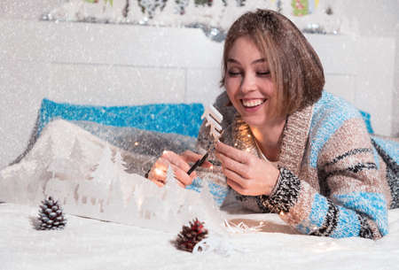a young girl with a smile is lying on the bed cuts a snowflake out of paper on a snow background.
