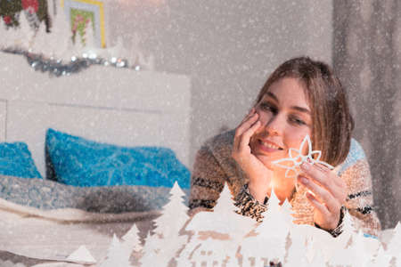 woman with a smile lying on the bed looking at a snowflake of paper.