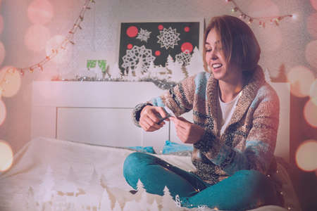 young girl sitting on the bed with a smile makes a snowflake out of paper in a warm tint. 写真素材