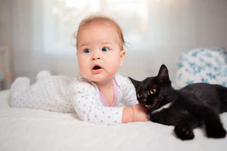 Portrait of a cute baby lying on a bed and playing with a cat.