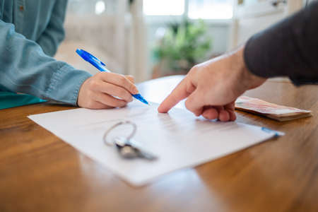 A realtor points to the contract for signing. Hands close-up. There are keys on the table. Rental and purchase of real estate. Stock fotó