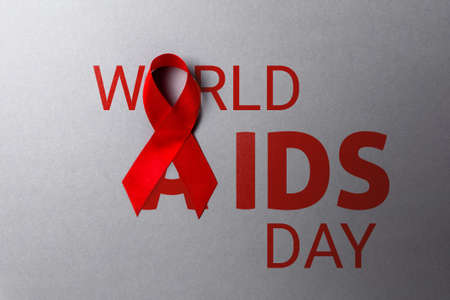 Red ribbon on a gray background. Text. Flat lay. The concept of world AIDS day. Stock fotó - 159659173