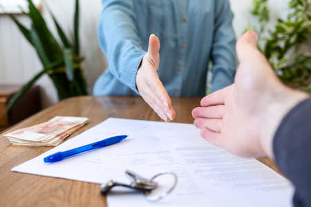 Realtor and buyer handshake. Close up of hands. On the table are money, keys and documents. Rental and purchase of real estate.