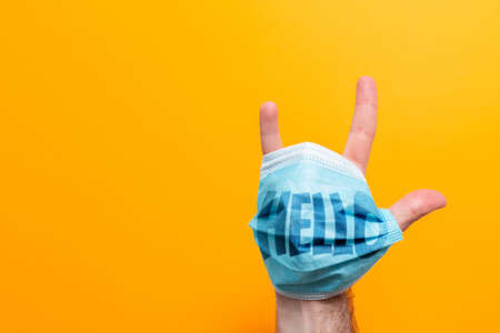 World Hello day. A male's hand with a mask on, fingers spread. The inscription on the mask Hello. Yellow background. The concept of protection from the virus. Stock fotó
