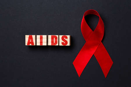 Red ribbon and wooden cubes with the word AIDS on a black background. Close up. Flat lay. The concept of world AIDS day.
