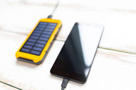 Concept of modern technologies. Smartphone with a black screen, charged from a portable solar charger. White wooden background with stripes. Close up. Flat line.