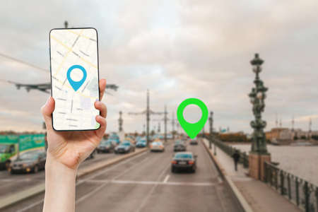 A female's hand holds a smartphone with an online map app. In the background is a road with car and green location icon.Concept of online navigation and GPS. Stock fotó