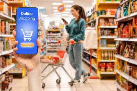 A person's hand holds a mobile phone, with a shopping basket on the screen. In the background, a woman is pushing a grocery cart, in a blur. The concept of online shopping.