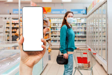 A person's hand holds a mobile phone, with a shopping basket on the screen. In the background, a woman wearing medical mask in a supermarket, in a blur. Mock up. The concept of online shopping.