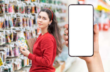 A person's hand holds a mobile phone, with a shopping basket on the screen. In the background, a pretty woman selects digital products, in a blur. Mock up. The concept of online shopping.