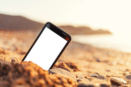 The concept of the photos on the phone. The smartphone lies buried in the sand on the beach, and takes a photo of the beach in the background. Mock up.