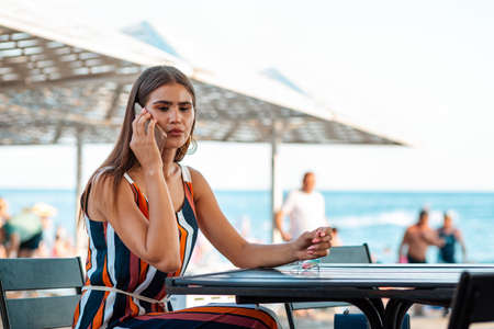 Communication. A tanned woman with a serious look is sitting in a summer cafe on the beach and talking on the phone. Concept of business.