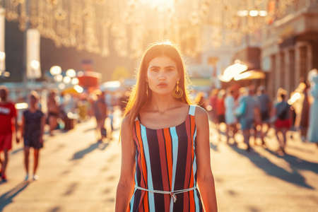 Portrait of a tanned woman in dress walking down the street. In the background, the sunset light and people in a blur. Concept of social advertising, business and psychology. Stock fotó