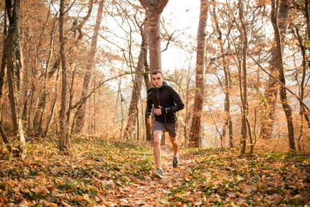The concept of sports and cross-country running. A man in sports clothes is engaged in intensive running on forest paths. The trunks of the trees in the background. Stock fotó