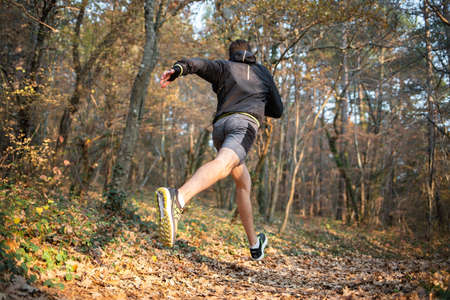 The concept of sport and healthy lifestyle. A young slender man in sports clothes is engaged in a fast run along a wooded path strewn with leaves. Rear view. Stock fotó - 159670211