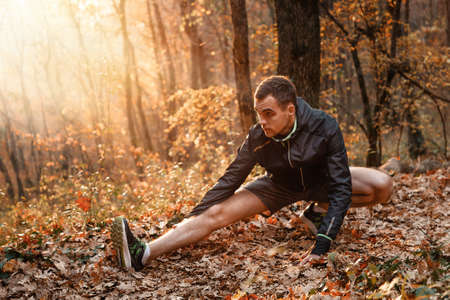 Concept of sport and active lifestyle. A young man is engaged in warm-up, fitness in the autumn forest. Sunlight. Stock fotó - 159662292