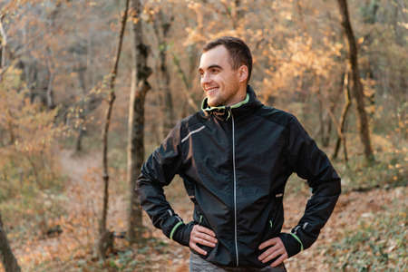 Concept of sport and active lifestyle. A young man in a black tracksuit, posing with a smile in the autumn Park.