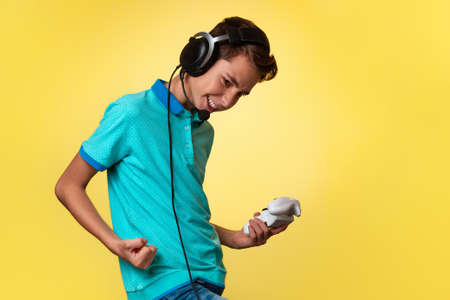 The concept of virtual and computer games. A teenage boy in a blue t-shirt and headphones, with a joystick in his hands, rejoices in winning the game. Yellow background. Copy space.