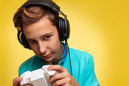 The concept of virtual and computer games. A portrait of teenage boy in a blue t-shirt and headphones, with a joystick in his hands, playing Internet games.