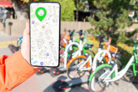 woman's hand holds a smartphone and shows an app with an online map. A bicycle parking lot is in the background. Concept of modern technologies and rent of environmentally friendly urban transport.