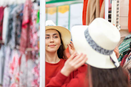 A pretty Caucasian woman tries on a straw hat in front of a mirror in a store. Rear view, face reflected in the mirror. Shopping concept.