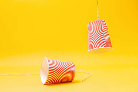 Two red paper cups, with the rope torn off. Children's homemade toy-walkie-talkie. Yellow background. Copy space. Close up. The concept of interrupting and disconnecting communication.